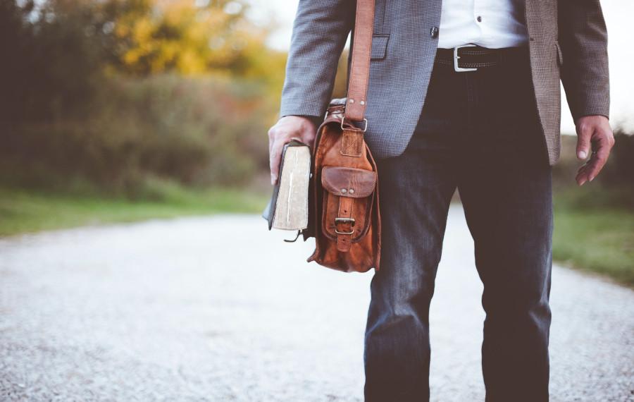 Mann auf der Straße mit Buch und Tasche
