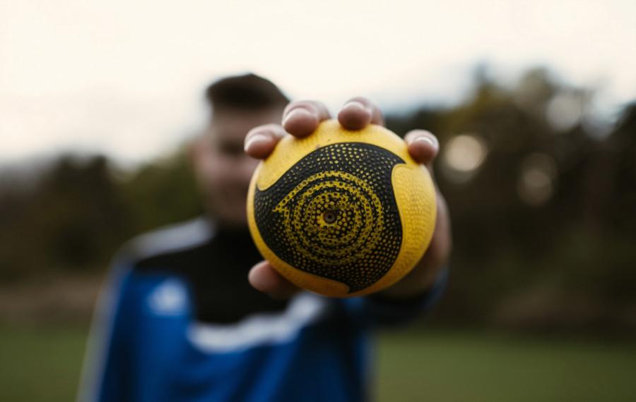 Mann mit gelben Ball in der Hand